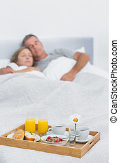Peaceful couple sleeping with breakfast tray on bed at home...