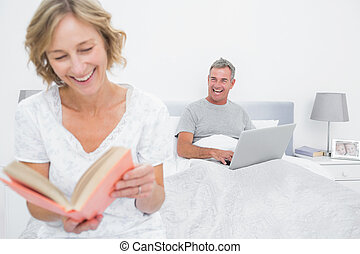 Woman reading book while husband is using laptop in bedroom...