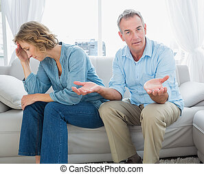 Arguing middle aged couple sitting on the couch with man...