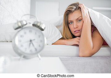 Exhausted blonde looking at camera with alarm clock in...