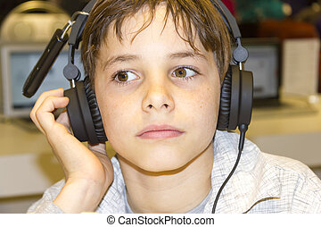 Portrait of a sweet young boy listening to music on...