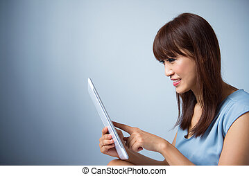 Asian woman reading a tablet pc