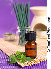 Aromatherapy - Bottle of essential oil, mint leaves and...