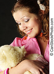 Maternal instinct - Pretty young woman embracing teddy...