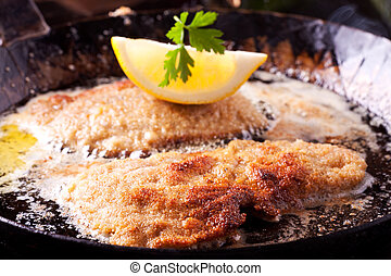 wiener schnitzel frying in a pan