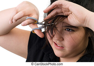 Hair Cut - A young girl trying to cut her own hair with a...