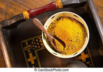 Yellow Curry Powder - Ceramic bowl filled with yellow curry...