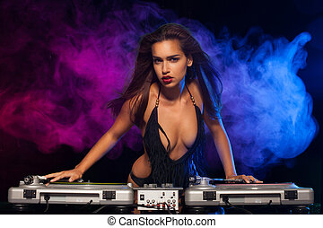 Glamorous sexy busty DJ at work mixing sound on her decks at...