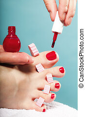 foot pedicure applying red toenails on blue - foot pedicure...