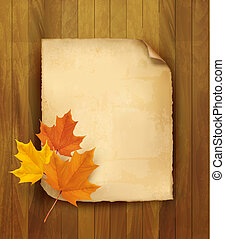 Sheet of paper with autumn leaves on wooden background....