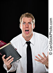Anguished young man holding bibles - Young man in a white...