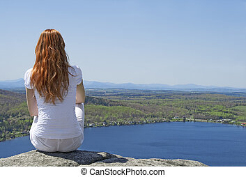 Young woman on top of a mountain - Young woman sitting on...