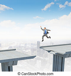 Ready to take a risk - Businessman jumping over a gap in the...