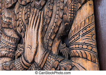 Wooden carving of Thailand greeting Wai