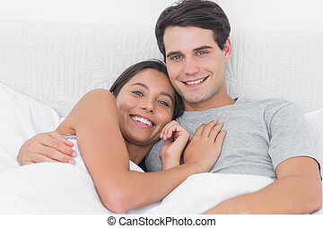 Woman embracing her boyfriend in bed in the bedroom