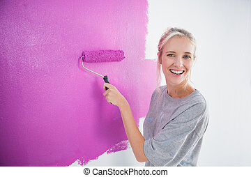 Laughing woman painting her wall in pink and looking at...