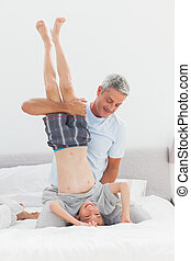 Father holding his son upside down having fun at home in...