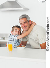 Smiling little boy giving hug to his father during breakfast...
