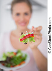 Woman with salad dish and salad on foreground