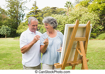Smiling retired woman painting on canvas with husband and...