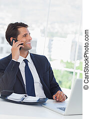 Cheerful businessman having a phone call in his office