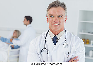 Experienced doctor posing in bright surgery with doctor...