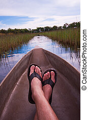 Man relaxing in a canoe point of view - mans feet relaxing a...