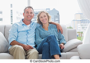 Happy couple relaxing on their couch smiling at camera at...
