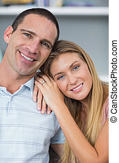 Cute couple sitting on the couch smiling at camera