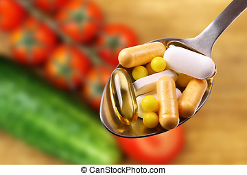 dietary supplements - spoon with tablets and capsules on...