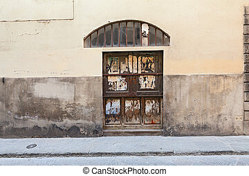 wooden door in the old town - stained grunge wall, old...