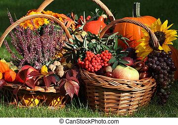 Autumn goodies in wicker baskets on green grass