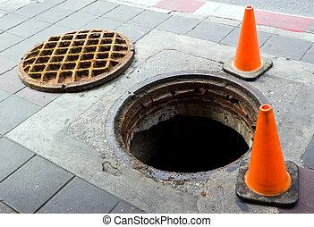Manhole on the footbath near street - Manhole cover open on...
