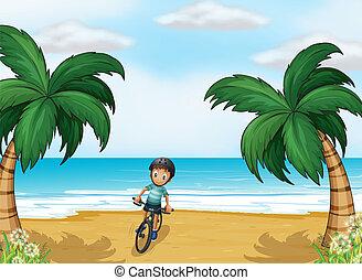 A boy biking at the beach