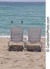 Two beach chairs and swimmers - Two beach chairs at the...