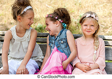 Laughing kids sitting on wooden bench. - Portrait of...