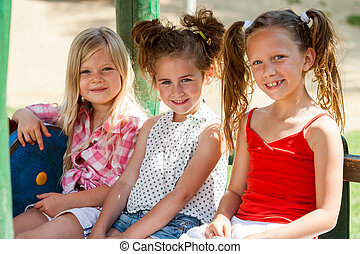 Three little girl friends in park. - Close up portrait of...