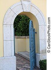 Open green gate in stucco wall - Open green metal gate in...