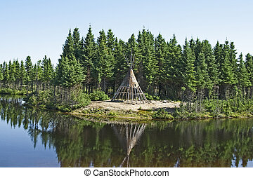 Native American tipi on a lakeshore - Traditional Native...