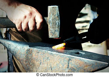 Blacksmith at work - Blacksmiths working process on metal at...