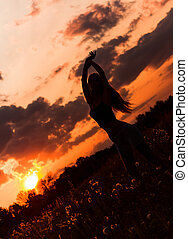 Silhouette of dancing young girl against the sunset sky
