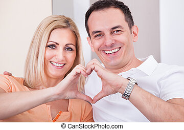 Happy Mid-adult Couple Forming Heart Shape Together -...