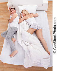 Uncomfortable Husband Sleeping With Wife On Bed