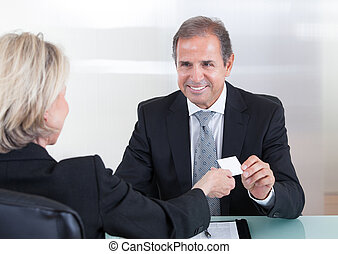 Businesspeople Exchanging Visiting Card In Office - Happy...