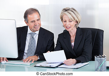 Mature Businessman And Businesswoman At Work - Happy Mature...