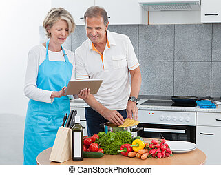 Mature Couple Using Tablet While Cooking - Mature Man And...