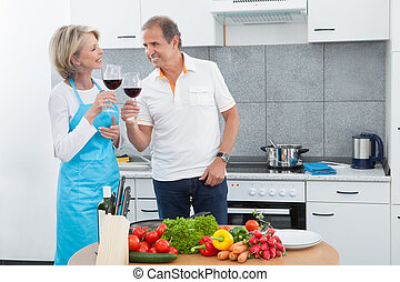 Happy Mature Drinking Wine In Kitchen - Happy Mature...