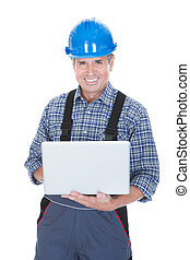 Worker wearing hard hat and using laptop