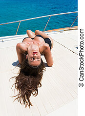 Young woman on her private yacht - Young woman suntanning on...