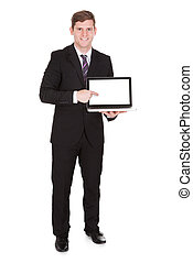 Happy businessman pointing on laptop